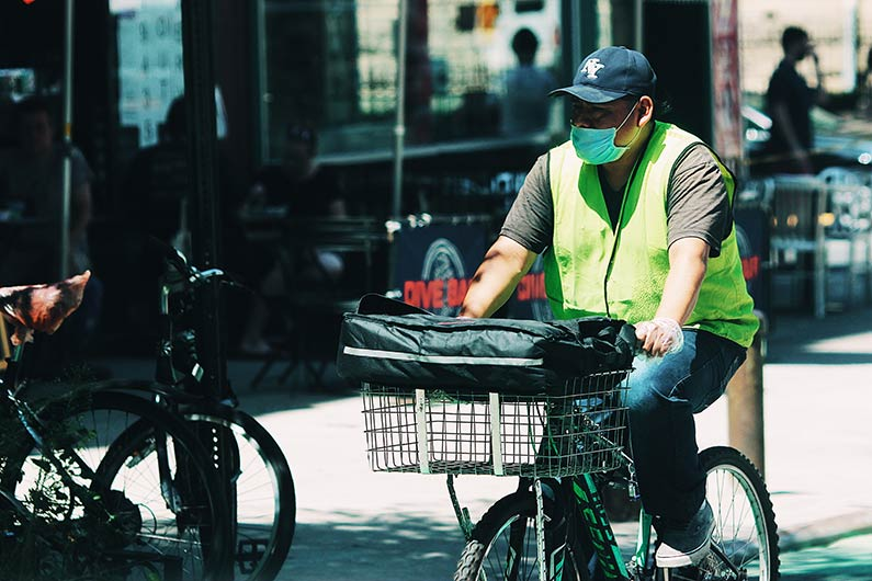 man on a bike delivering goods for the courier business he works for