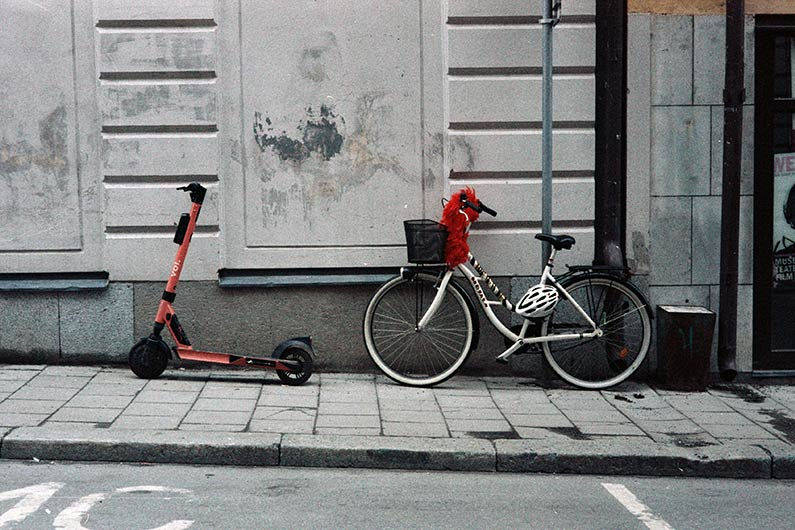 ebike and electric scooter parked next to each other on a European city street
