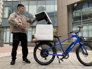 A courier packs his keego kg2 delivery ebike