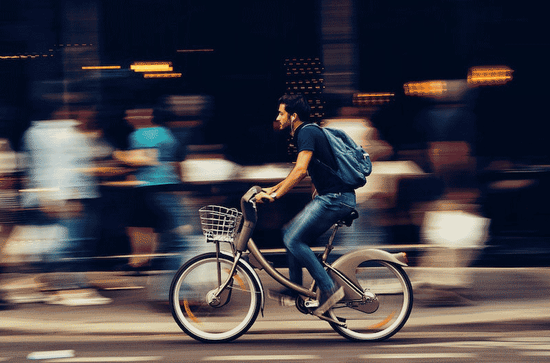 Man on an ebike cruising down a busy street, pedal assist engaged fully